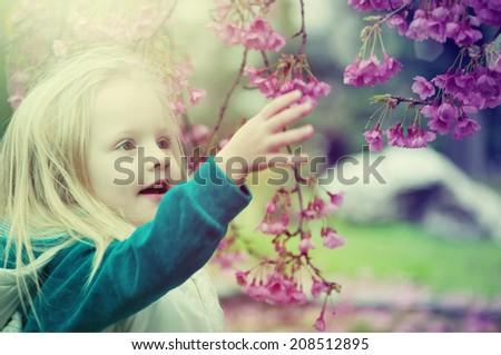 Little girl in the blooming garden - stock photo