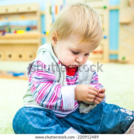 little girl in the classroom early development plays with bright toys - stock photo