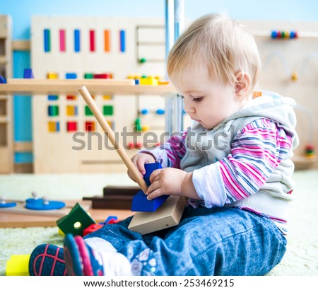 little girl in the classroom early development plays with numerous bright toys - stock photo