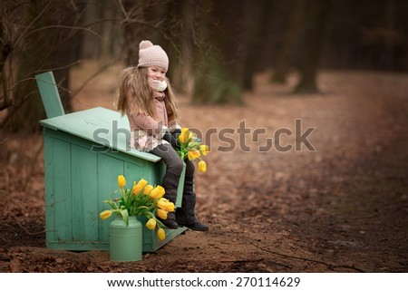 little girl in the coat and hat is sitting on the green box and holding green can with yellow tulips flowers in the park at spring time - stock photo