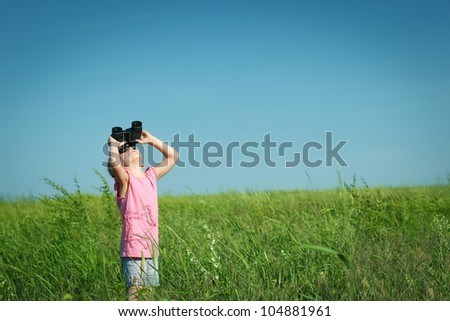 Little girl in the field looking up in the sky through the binoculars - stock photo