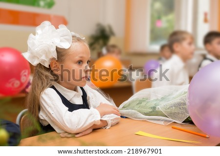 Little girl in the first day of school in the classroom. Russia.  - stock photo