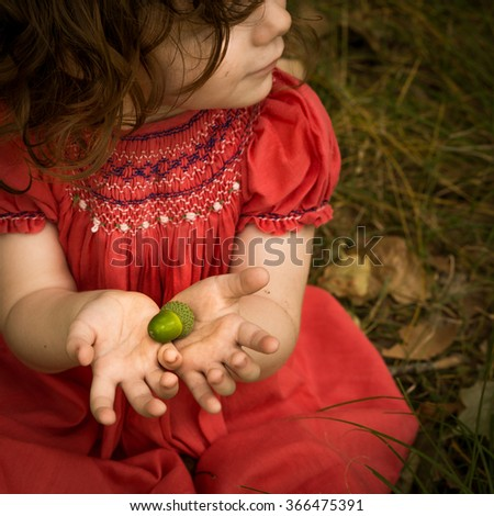 Little girl in the forest. Oak seed in their hands.  The talles  Oak tree in the forest was once just a little nut that held its ground Dress boho style - stock photo
