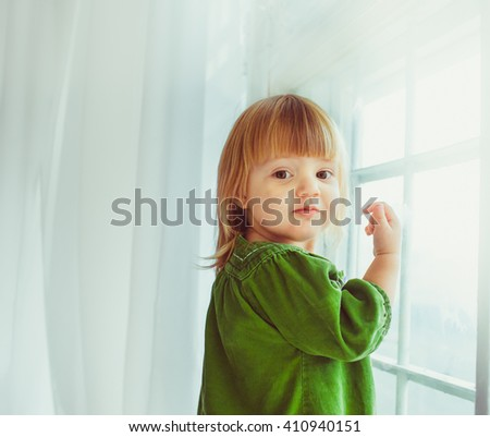 Little girl in the green dress next to the window