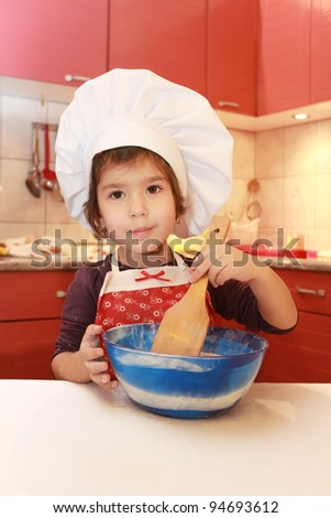 Little girl in the kitchen - stock photo