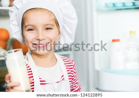 little girl in the kitchen drinking milk - stock photo