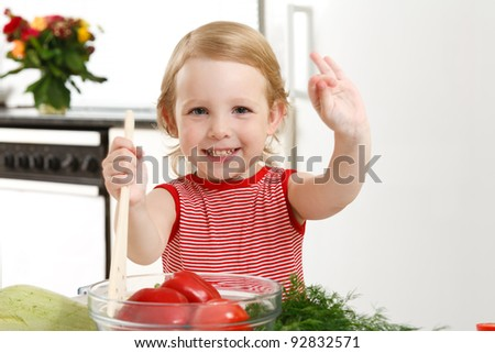 little girl in the kitchen preparing a salad - stock photo