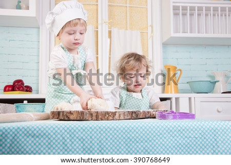 Little girl in the kitchen sculpts dough - stock photo