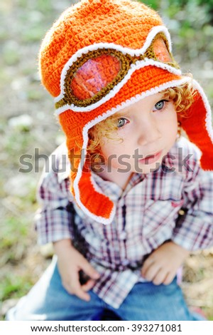 little girl in the orange cap of the pilot and flight goggles - stock photo