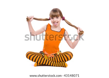 Little girl in the orange dress is putting out one's tongue and is sitting on the floor. Portrait of an attractive young teenager is smiling in orange over white background. - stock photo