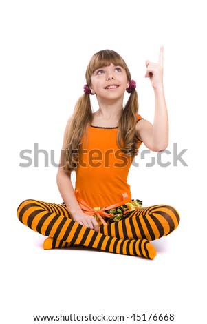 Little girl in the orange dress is sitting on the floor and pointing to up. Portrait of an attractive young teenager is smiling in orange over white background. - stock photo