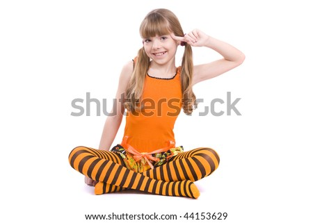 Little girl in the orange dress with finger near her head is sitting on the floor. Portrait of an attractive young teenager is  playing the fool and smiling in orange over white background. - stock photo