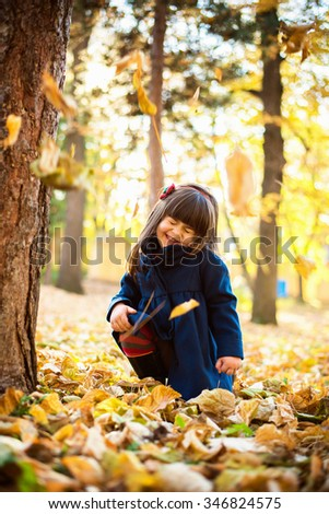 Little girl in the park Cute little girl playing in the park at autumn sunny day. She is making a face,having fun - stock photo