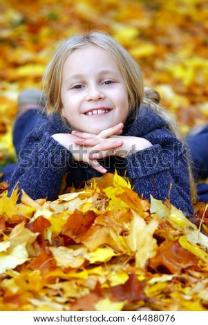 Little girl in the park in autumn