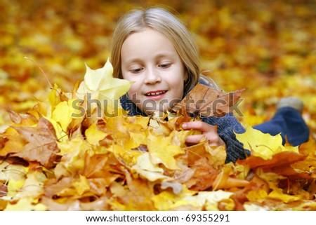 Little girl in the park in autumn - stock photo