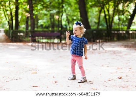 Little girl in the park looking at the phone