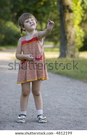 Little girl in the park wearing dress appreciating the stone she holding in her hand - stock photo