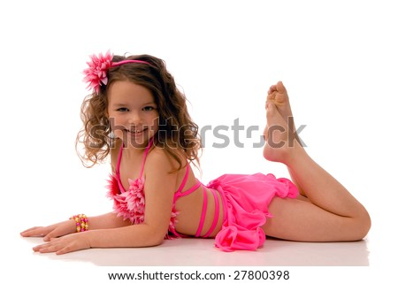 little girl in the pink bathing suit lying on the floor - stock photo