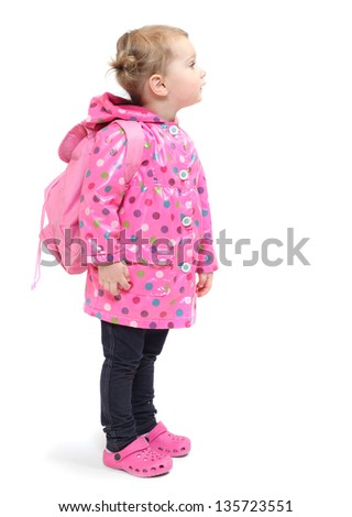 Little girl in the raincoat with backpack going to school. - stock photo
