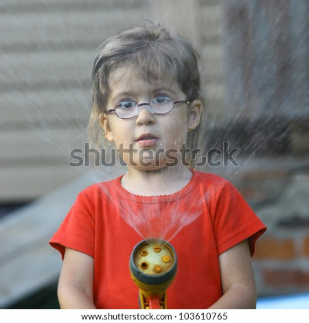 Little girl in the red shirt pours water from a hose - stock photo