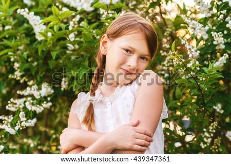 Little girl in the spring garden at sunset - stock photo