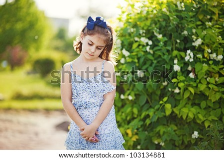 Little girl in the summer garden - stock photo