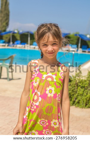 Little girl in the summer on a background of blue pool