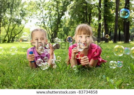 Little girl in the summer park blowing bubbles - stock photo