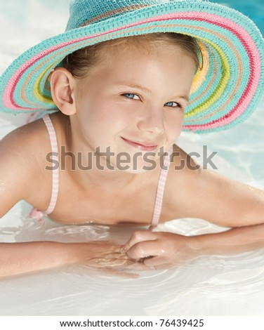 little girl in the swimming pool in hat - stock photo