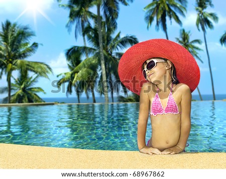 little girl in the swimming pool in hat and sun glasses - stock photo