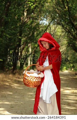"Little girl in the wood looks up. the fairy tale "" Red Riding Hood"""