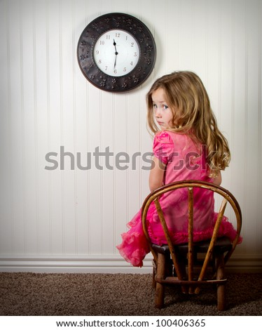 little girl in time out or in trouble looking, with clock on the wall - stock photo