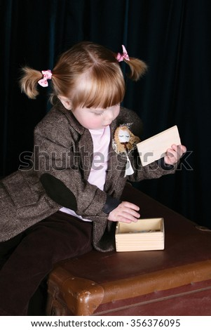 Little girl in vintage attire playing with a puzzle - stock photo