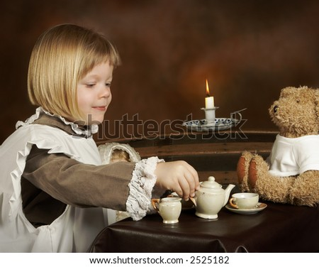 Little girl in vintage dress sharing tea with her teddy bear