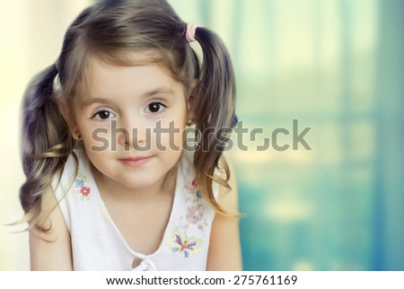 Little girl in white cloth looking at camera. Small child closeup on blue indoors background. - stock photo