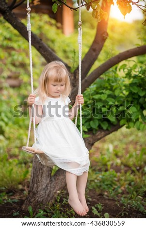 Little girl in white dress sitting on a suspended swing in the forest in summer