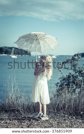 little girl in white dress with white sunshade at the seaside