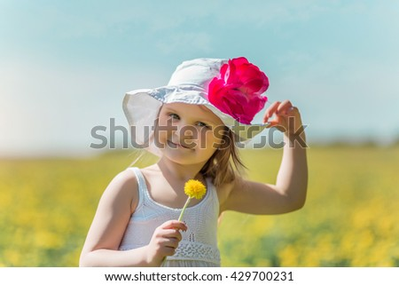 Little girl in white hat with flower in hand in a summer field. Closeup - stock photo