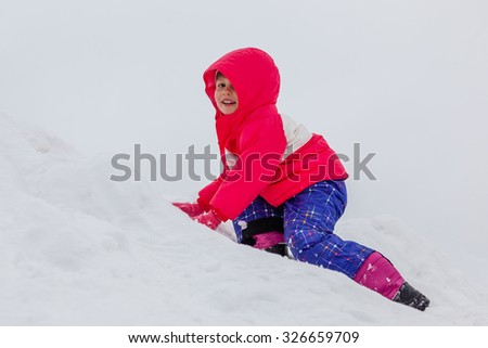 Little girl in winter clothes climbing snow hill. Walking with kids in cold snowy weather. Concept of healthy well being. - stock photo