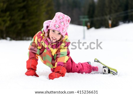 Little girl in winter outfit fell while skiing. Kid is lying in the snow with skis smiling. Happy ski experience in resort. Skiing accident. - stock photo