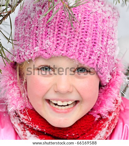 Little girl in winter pink hat in snow. - stock photo