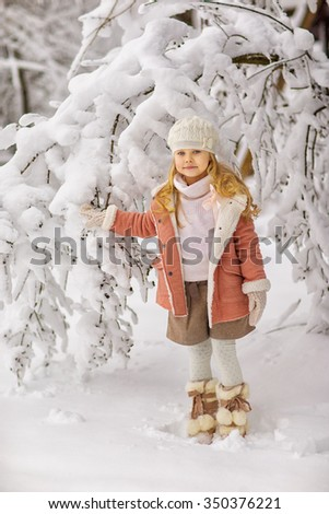 little girl in winter snow-covered park