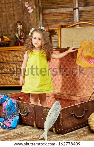 Little girl in yellow dress stand in opened old big ragged fiber suitcase lying on floor in room