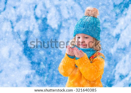 Little girl in yellow knitted sweater and blue hat catching snowflakes in winter park. Kids play outdoor in snowy forest. Children catch snow flakes. Toddler kid playing outside in snow storm. - stock photo
