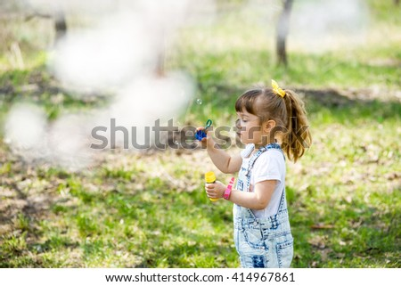 little girl inflates soap bubbles in spring in the garden