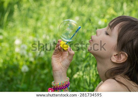 Little girl inflates soap bubbles in the park. How to inflate the bubble. blowing bubbles
