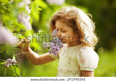 little girl inhales the aroma of lilacs - stock photo