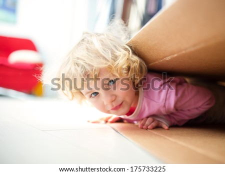 Little girl inside a paper box  - stock photo