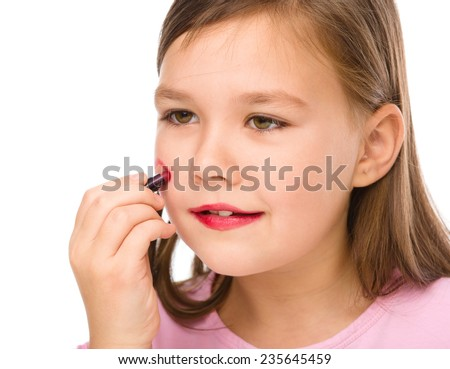 Little girl is applying lipstick on her cheek, isolated over white - stock photo