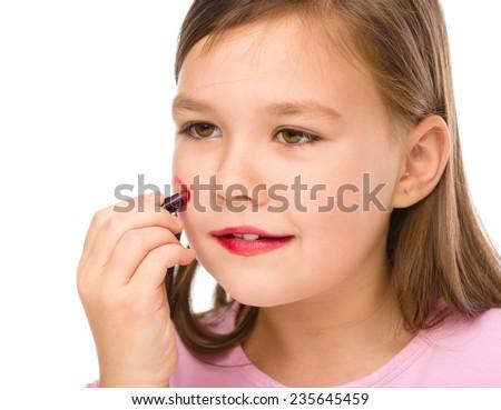 Little girl is applying lipstick on her cheek, isolated over white - stock photo